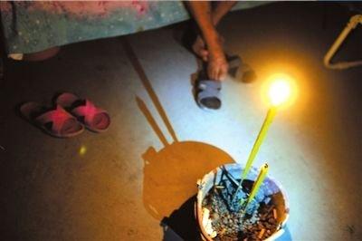 26日,芦山县龙门乡隆兴村村民张德文在帐篷中点燃香烛。他的妻子在地震中不幸遇难。