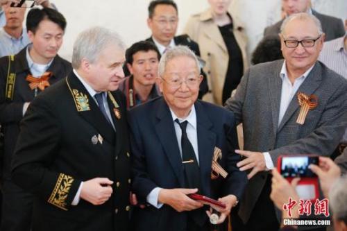 4月15日,俄罗斯驻华大使安德烈·杰尼索夫(左)与获颁奖章的中国老兵合影。中新社发 王骏 摄