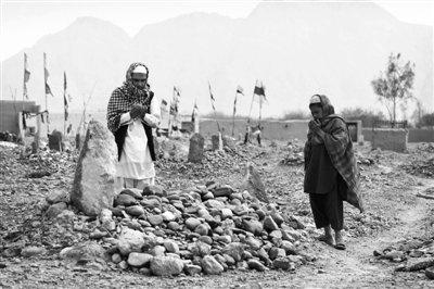 24日,阿富汗坎大哈省,两名当地村民在堆满石块的坟前为枪击案遇害者祈祷。