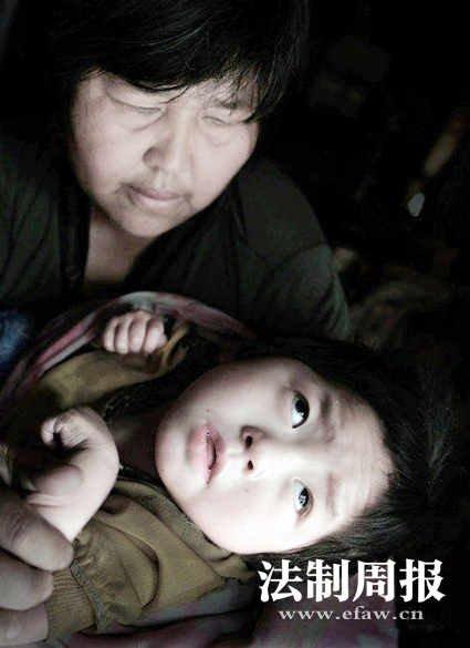 2011年9月,河南兰考,袁厉害正在照看一名脑瘫的孩子。卢广 图