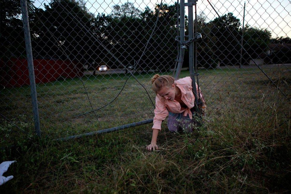 当地时间2010年10月19日,美国得克萨斯州奥斯汀,17岁的高三学生Dandilion Olson抄近道爬过教堂栅栏,准备和妹妹以及妹妹的朋友在湖中划桨。