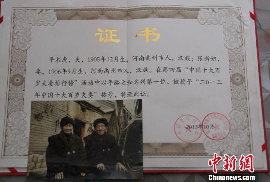"""中国老年学会为老夫妻颁发的""""中国最长寿夫妻""""证书。 朱清 摄"""