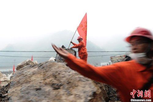 救援人员在山体塌方地段指挥车辆通行