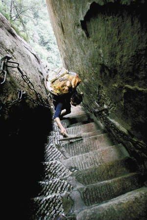 """华山第一险道""""千尺幢""""与地面几乎呈80度,何天武背着60多斤的菜,一只手还要拿着拐杖,只能艰难爬行。"""