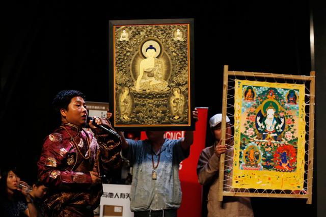 图为:热贡唐卡画师格桑达娃展示唐卡精品