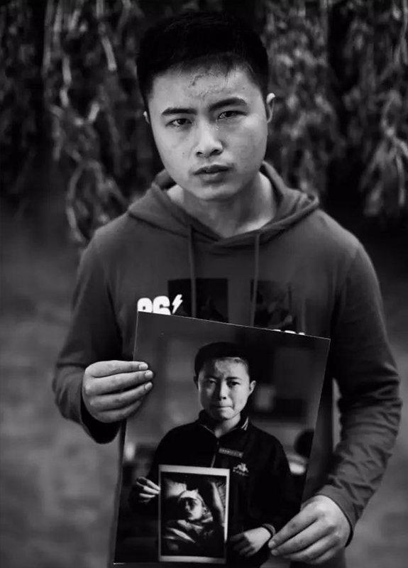 """2014年5月4日,四川省什邡市湔氐镇龙泉村。""""汶川地震""""6周年,地震幸存者20岁的姜刘拿着地震1周年时拍摄的肖像。现在,他患有""""双相情感障碍""""。"""