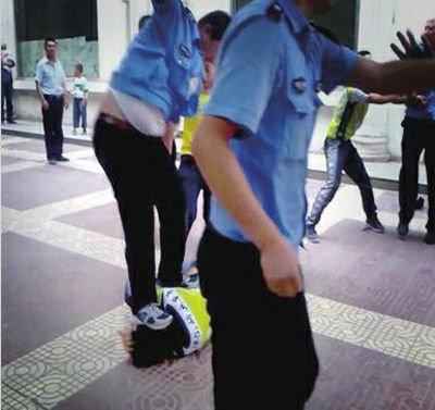 """网曝延安城管""""暴力执法""""视频。男子被打倒在地,一城管( 体型偏胖) 并未罢休,双腿跳起踩向青年头部(截屏照片)"""