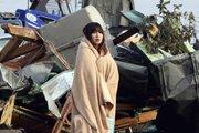 女孩裹着毯子站在震后的瓦砾旁
