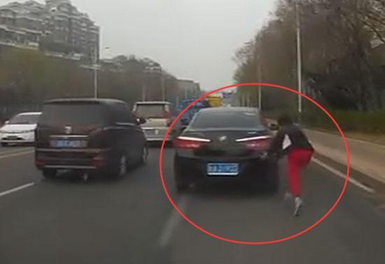 该女子为碰瓷在马路上追着车跑