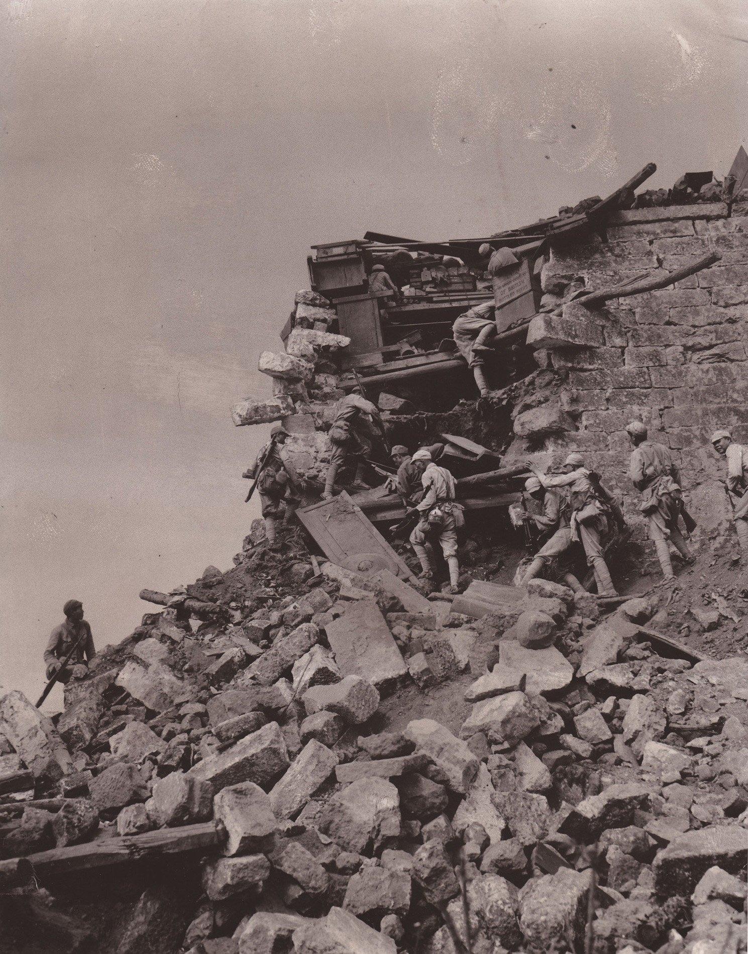 中国士兵正在攀爬损毁了的城墙,远处的硝烟是盟军投掷的手榴弹所致。盟军解放了缅甸以东的第一座中国城市。经过5周的血战,古老的玉石之乡腾冲终于摆脱了日本的统治。弗兰克・坎德拉尔拍摄于1944年10月4日,收录于战争影像库。