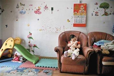 6月14日,未婚妈妈于军的家里。女儿悦悦抱着兔子玩偶,在听妈妈手机上的儿歌,这个4岁女孩喜欢兔子。