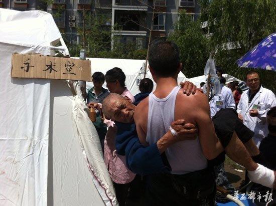 儿子抱着父亲在芦山临时帐篷医院等待手术(图)