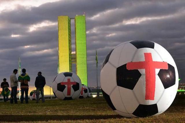 巴西民众国会前放12个巨大足球 抗议世界杯花销