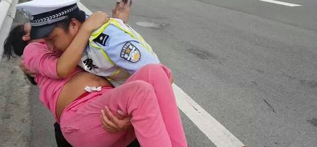 交警将孕妇抱上警车。