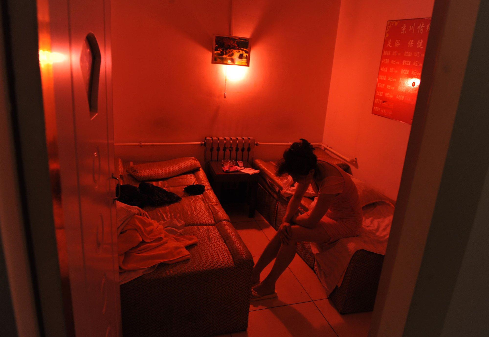 一名小姐被控制在昏暗的房间内。图片与文章人物无关。图片来源/视觉中国