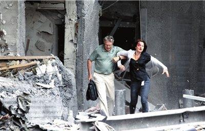 一名受伤妇女被搀扶出爆炸大楼。新华社/美联