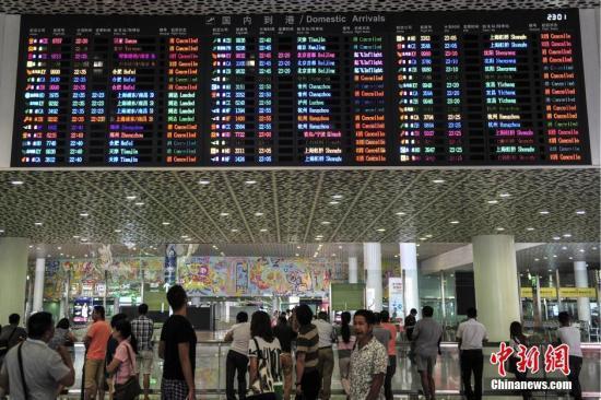 """8月1日,深圳机场,到达大厅的显示屏上滚动播放着被取消航班的信息。当日,受台风""""妮妲""""影响,深圳机场启动三防红色预警,各航空公司已在深圳机场取消8月1日至2日两天进出港航班140班。 中新社记者 陈骥旻 摄"""