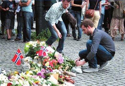7月23日,一名挪威男子在奥斯陆大教堂前举行的悼念仪式上向死去的亲人献花。新华社发