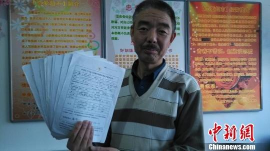 图为王长春展示今年收到的9位志愿者签订的《中国红十字会人体器官捐献志愿者申请表》。两年里经有超过20人同意了遗体捐赠。刘洋摄