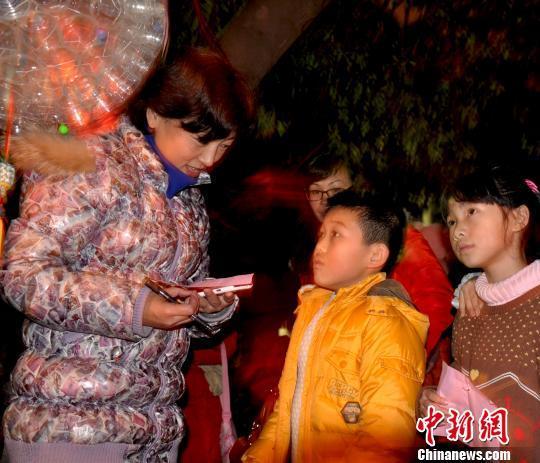 """广西柳州市柳南区实验小学就低年级的期末考试就进行了创新改革,将考试变成""""欢乐园""""主题活动,分为自制花灯,文艺演出,赏花灯、猜灯谜三部分。图为学生们在猜灯谜答题。乔毅鸿摄"""