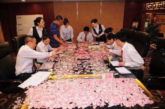 5月3日,成都,中国银行四川省分行工作人员正在整理林兆强带来的5万元残币,试图还原这些现金