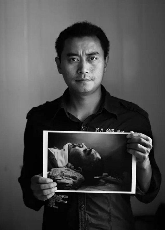 """2009年5月10日,四川省安县雎水镇。""""汶川地震""""1周年,地震幸存者30岁的李德强拿着地震后受伤躺在伤员专列上的照片。现在,他是一名货车司机。"""