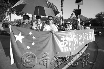 当地时间6月6日傍晚,习近平下榻的凯悦酒店旁边,当地华人举起国旗和横幅迎接。本报特派记者戴伟摄