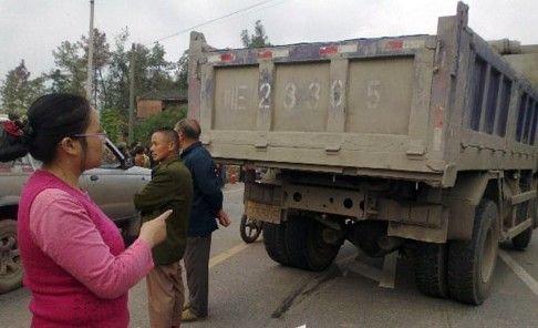 小孩的母亲向记者指认货车