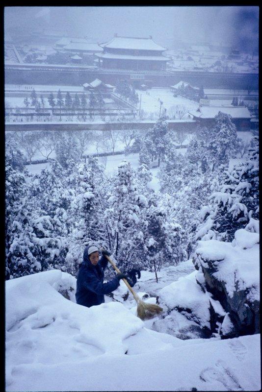 """故宫、景山、北海和鼓楼位于北京城的中心位置,景山中峰的万春亭虽然只有不到50米高,却可以南瞰故宫,北望鼓楼,西观北海。图为1964年,景山万春亭南侧正在清理积雪的工作人员。这场景和林语堂在《北平的冬天》中的文字很有同感:""""一夜北风寒,大雪纷纷落,那景致有得瞧的。但是有几个人能有谢道韫女士那样从容吟雪的福分。所有的人都被那砭人肌肤的朔风吹得缩头缩脑,各自忙着做各自的事。"""""""