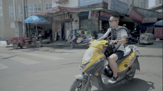 ▲《错位――亚洲跨性别者》剧照。小C每个星期都要骑电瓶车去贵阳市人才市场找工作,然后一起接女友下班回家。