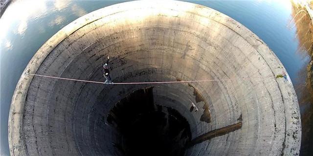 男子挑战极限恐惧 60米深黑洞上走绳索(组图