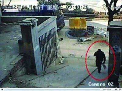 嫌疑人手拎蓝色纸袋,进入东门街小区大门。视频截图