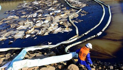11月25日,青岛,工人正在清理海面原油。