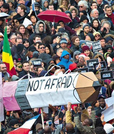 """参加游行的民众高举写着""""不恐惧""""的铅笔模型,致敬恐袭遇难者。"""