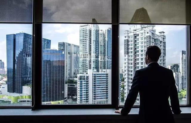 一位外国白领从他豪华的办公区远望现代私人住宅区。他住在新加坡三年,却从未见过政府廉价组屋里的样子。摄影/Amrita Chandradas