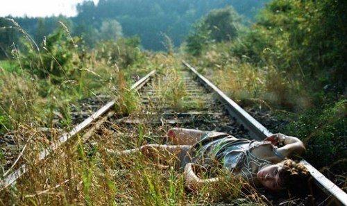 希格丽德扮演受暴力迫害的女性,满身伤痕,横躺在铁轨上。