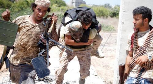 2016年7月31日,利比亚团结政府部队在苏尔特与伊斯兰国武装分子作战。政府军的一名战士掩护另外一名战士背着伤员撤离。(路透社)
