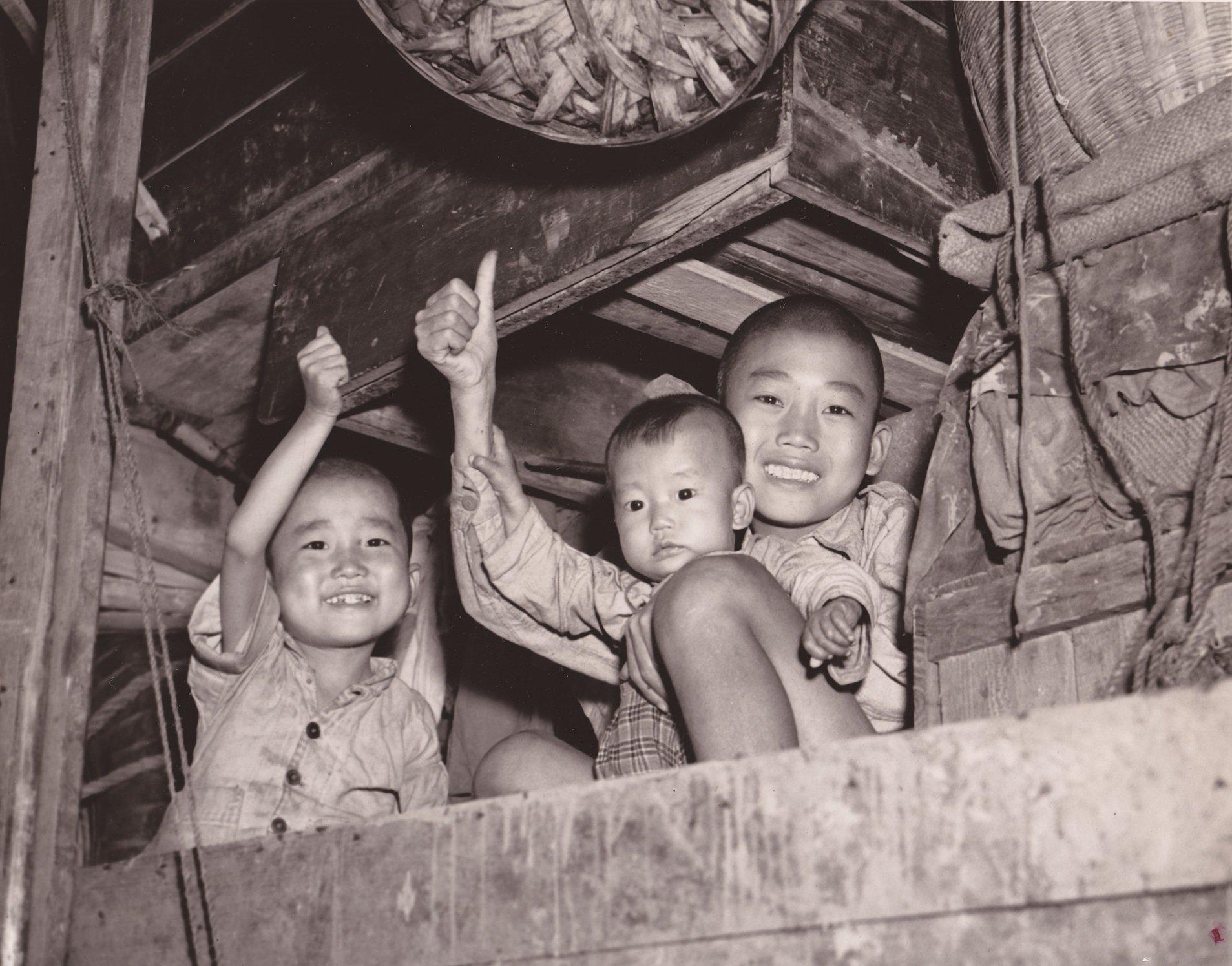 """小朋友彰显中国式的不屈不挠精神,给摄影师摆出骄傲的""""顶好""""手势。拍摄于1944年11月10日。"""
