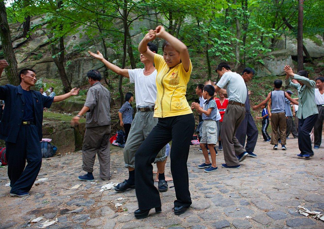 """朝鲜的国庆日9月9日当天,平壤的公园里到处都是野餐的家庭,我可以自由地在附近观光,当地人会分享一些烧酒和吃的给我,请我和他们一起合影,还会拉手风琴,邀请我和他们一起跳舞。有个稍微大胆一些的人,上前问我来自哪里,当得知我是法国人时,在场女性们的眼睛都亮了,纷纷和我讨论起法国香水来。男人们则会说到齐达内,老人们告诉我他们在学校的时候就读过雨果的作品!我发现多数男生只和男生跳舞。我好奇地问起导游来,他不以为意地回答道:""""因为他们害羞啊!难道你会和陌生女性共舞吗?""""他简直无法想象如果邀请陌生女性跳舞后,接下来会发生些什么。"""