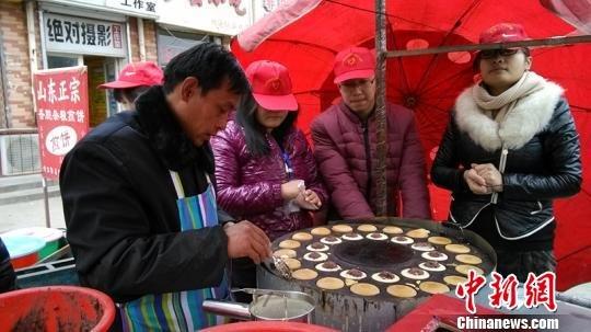 石家庄男子拉条幅卖饼救病妻 市民排队购买(图)
