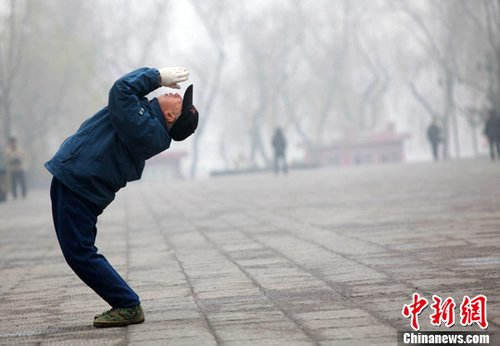 资料图:12月22日,山西太原,民众在雾天里晨练。在12月21日举行的2012年中国环境保护工作会议上,环保部部长周生贤表示,明年起,北京、天津、河北和长三角、珠三角等重点区域以及直辖市和省会城市将开展PM2.5和臭氧监测。中新社发 韦亮 摄
