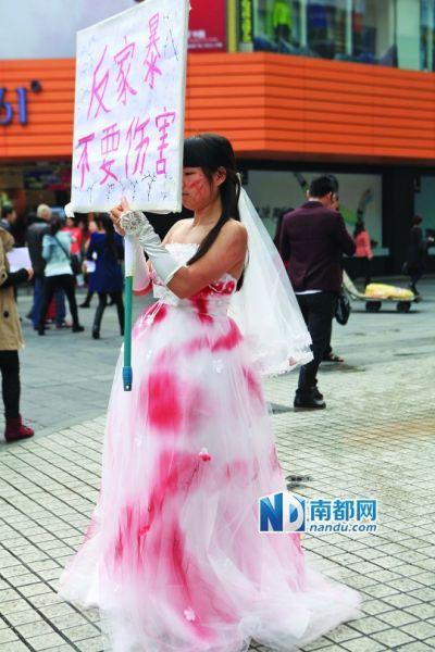 女子装扮受伤新娘 身着染红婚纱街头反家暴