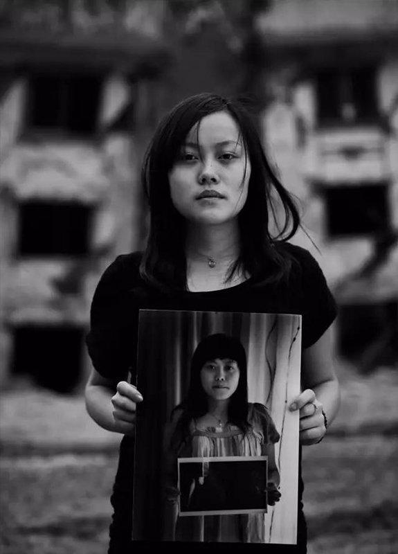 """2014年5月5日,四川省老北川地震遗址。""""汶川地震""""6周年,地震幸存者24岁的龚悦拿着地震1周年时拍摄的肖像。"""
