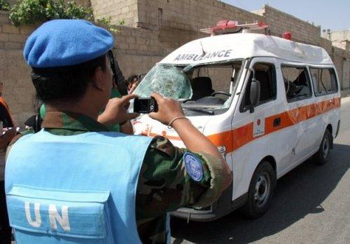 一名联合国监督团成员在大马士革郊区为一辆被毁救护车拍照