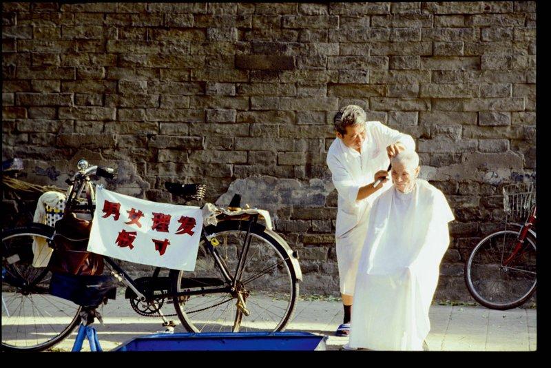 20世纪70年代,北京故宫城墙下的剃头师傅和他的老主顾。