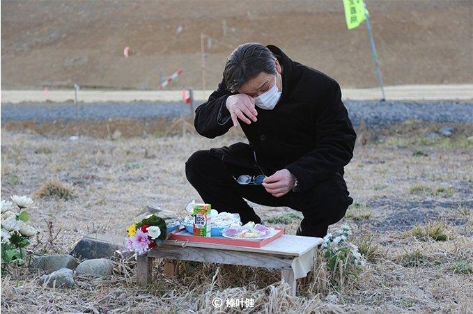 失去妻子的消防员在妻子遇难地祭祀。妻子遇难时,他正在扑灭因大地震引发的大火,此后他一直谴责自己未能救出她。
