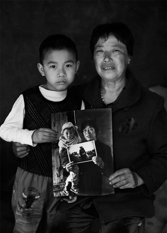 """2014年5月3日,四川省彭州市通济镇桥楼村。""""汶川地震""""6周年,地震幸存者65岁的曹良英和地震幸存者6岁半的孙子罗远航拿着地震1周年时拍摄的肖像。"""