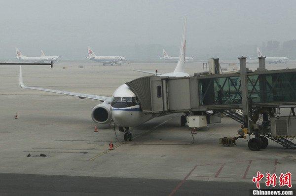 资料图:10月6日,北京首都机场停机坪被雾霾笼罩。当日,受严重雾霾天气影响,北京首都机场所有进出港航班一度全部暂停。而在最近更大范围的雾霾天气中,全国各地的航班更出现大面积延误。中新社发 李慧思 摄