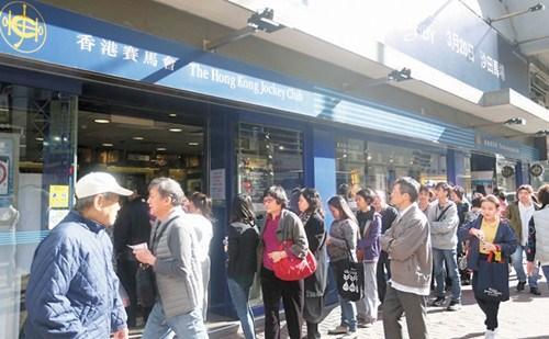 """大批市民在全港不同投注站大排长龙购买彩票争做""""亿元富翁""""。香港《文汇报》/莫雪芝 摄"""