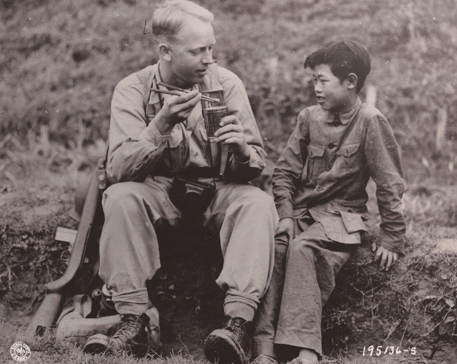在中缅印战场,来自北达科塔州的通信兵摄影师上等兵亚瑟・海吉用筷子吃美国野战口粮,身旁的小孩李田右(音)在教他使用筷子。海吉正在前往前线拍摄中国军队行动的影像途中停下来休息用餐。拍摄于中国,1944年5月6日。